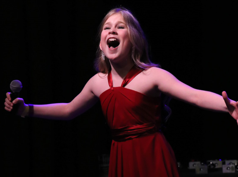 A picture of an North Texas Performing Arts student performing on stage.