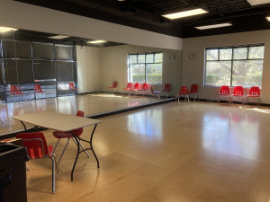Rehearsal room with table, wooden floors and mirrors