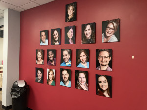 North Texas Performing Arts staff photos on red wall
