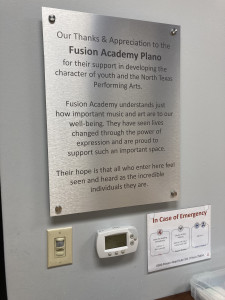 Metal sign recognizing sponsorship from Fusion Academy Plano