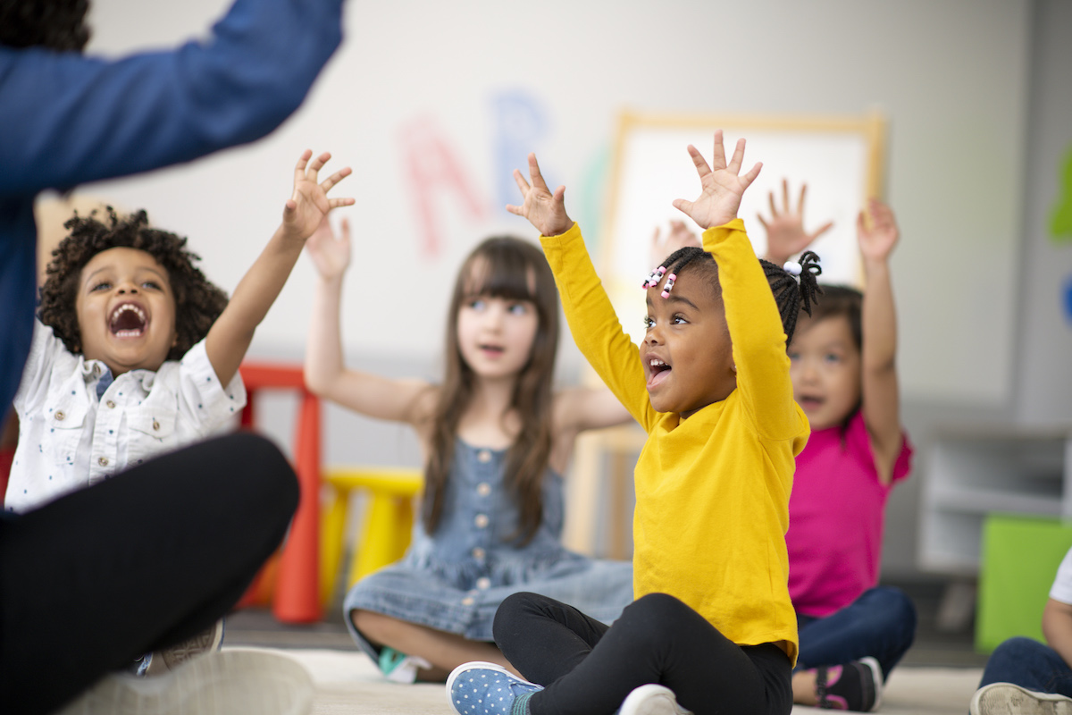 A multi-ethnic group of preschool students is sitting with their legs crossed on the floor in their classroom. The teacher is sitting on the floor facing the children. The happy kids are smiling and following the teacher's instructions. They have their arms raised in the air.